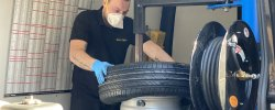 Mobile Tyres 2 U mechanic changing tyre in company van with mask on